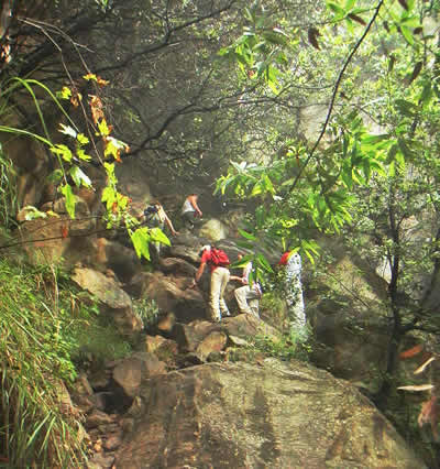 Hikers climbing boulders to Tangerine Falls on West fork of Cold Springs Trail